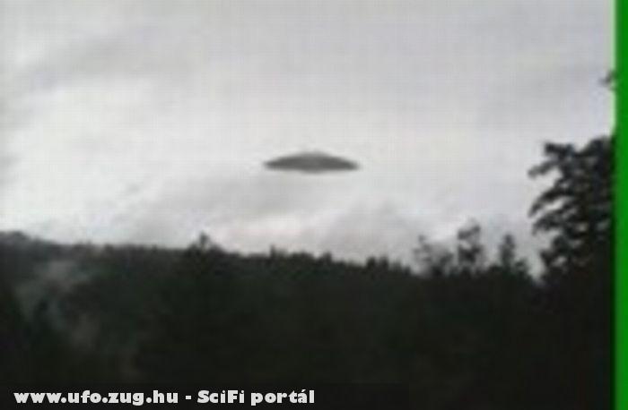 Egy teljesen jól kivehetõ UFO-t láthatunk egy erdõ felett lassan manõverezni